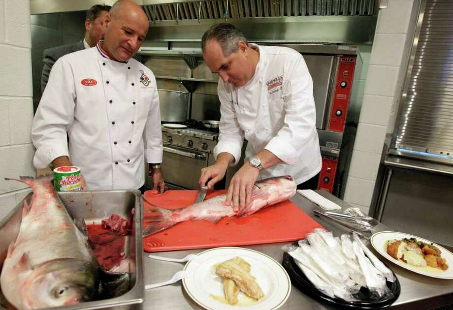 NAM Y. HUH : ASSOCIATED PRESS LOUISIANA CUISINE: Chef Tim Creehan, right, and chef Philippe Parola prepare the fish at the school. Parola says it's a great natural resource. Photo: Nam Y. Huh / AP