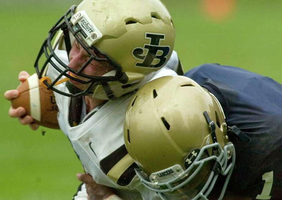 Joel Barlow's Joshua Tunick, left, runs the ball into Notre Dame's Daquan Coleman during their game at Notre Dame Catholic High School in Fairfield on Saturday, Sept. 24, 2011. Photo: Jason Rearick / The News-Times