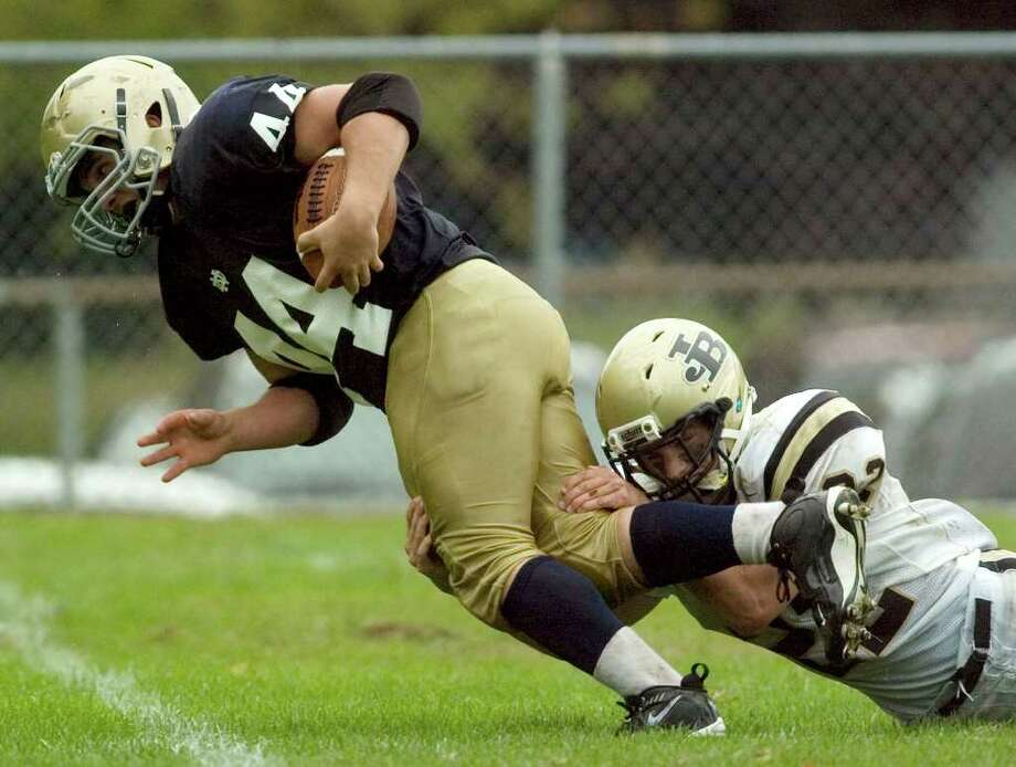 Notre Dame's Frank Zumbo, left, gets tripped up by Joel Barlow's Alex Lockwood during their game at Notre Dame Catholic High School in Fairfield on Saturday, Sept. 24, 2011. Photo: Jason Rearick / The News-Times