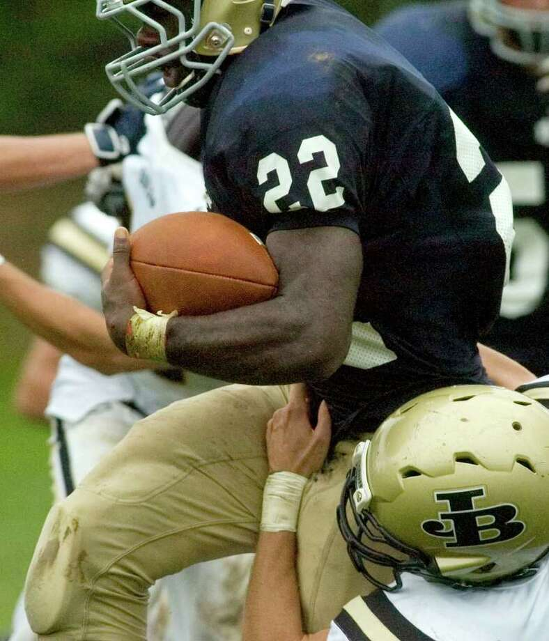Notre Dame's Nigel Beckford, top, tries to break through the tackle of Joel Barlow's Samuel Reed during their game at Notre Dame Catholic High School in Fairfield on Saturday, Sept. 24, 2011. Photo: Jason Rearick / The News-Times