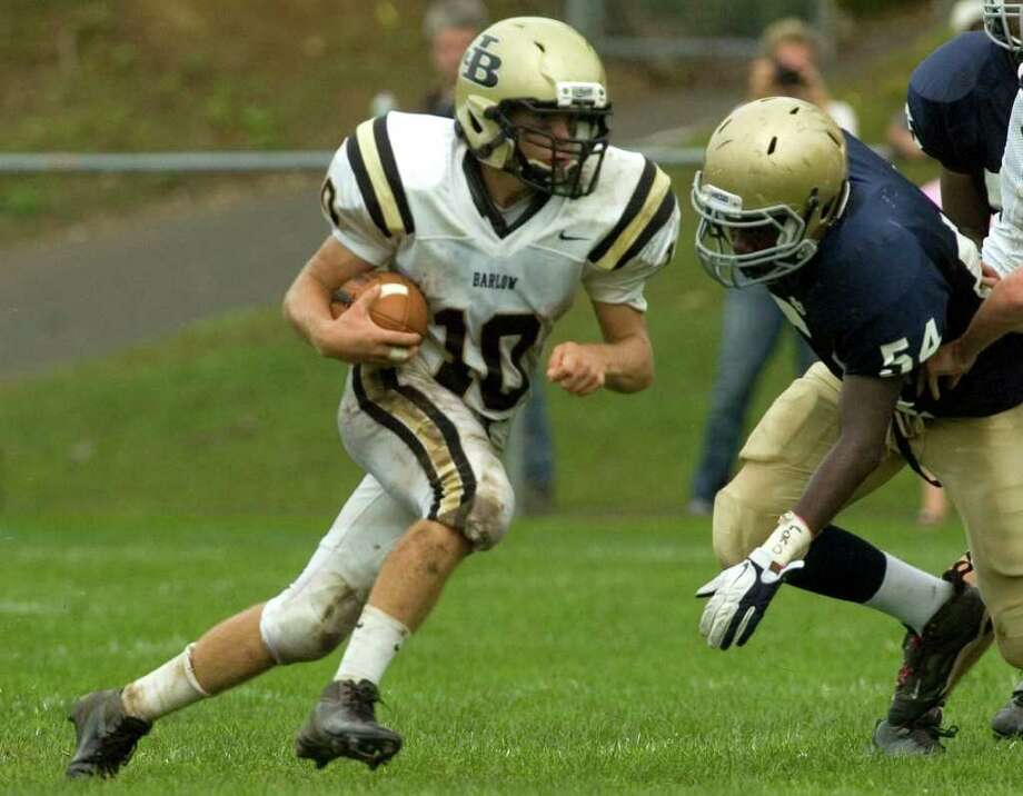 Joel Barlow quarterback Jack Shaban runs the ball up the middle with Notre Dame's Thomas Allen, right, in pursuit during their game at Notre Dame Catholic High School in Fairfield on Saturday, Sept. 24, 2011. Photo: Jason Rearick / The News-Times