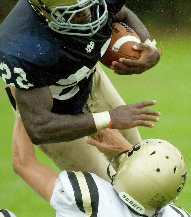 Notre Dame's Nigel Beckford, top, tries to run through the tackle of Joel Barlow's Samuel Reed during their game at Notre Dame Catholic High School in Fairfield on Saturday, Sept. 24, 2011. Photo: Jason Rearick / The News-Times
