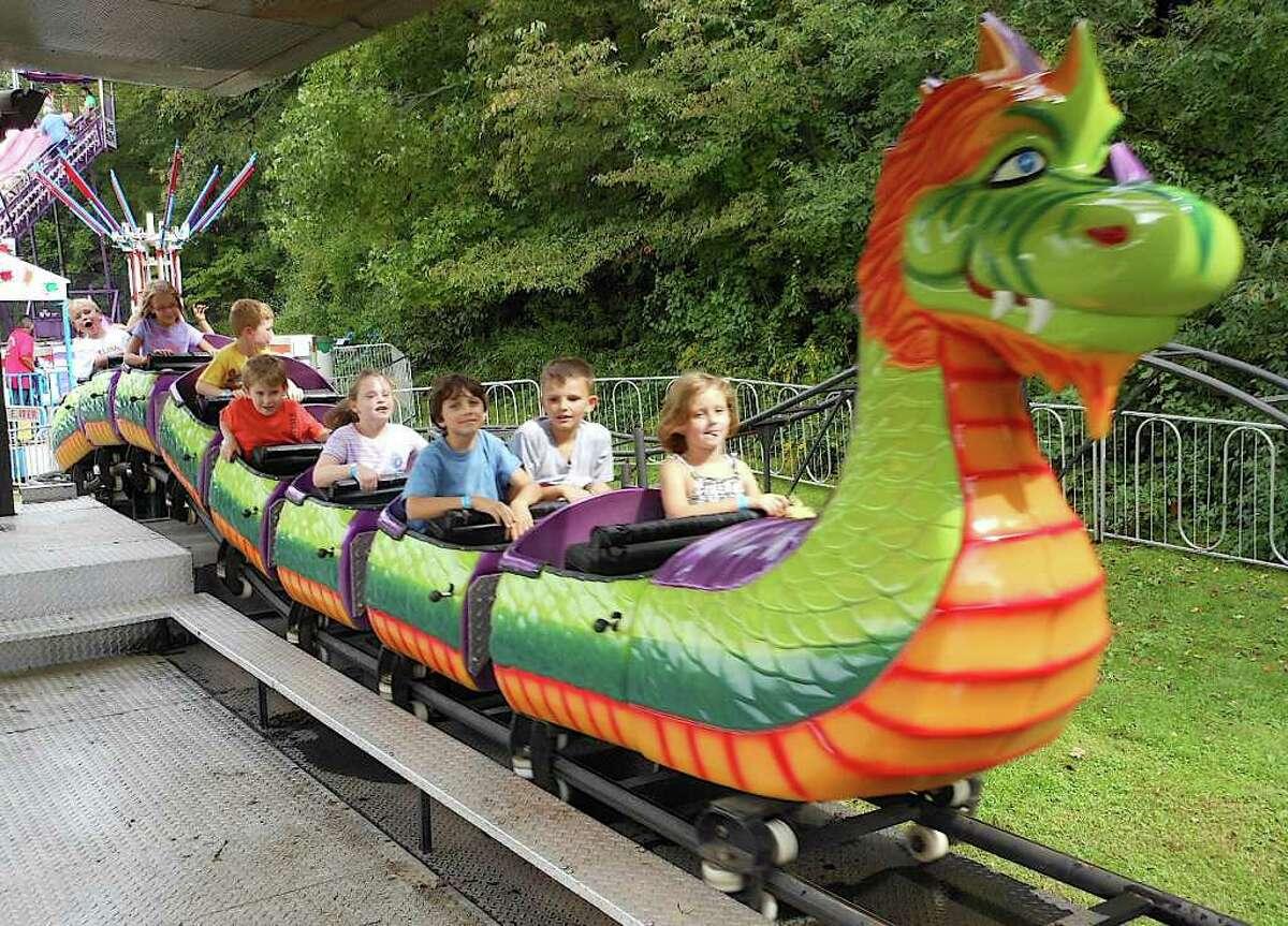 Kids enjoy the Dragon Wagon, one of many amusement rides Saturday at the annual Dwight School Fair.