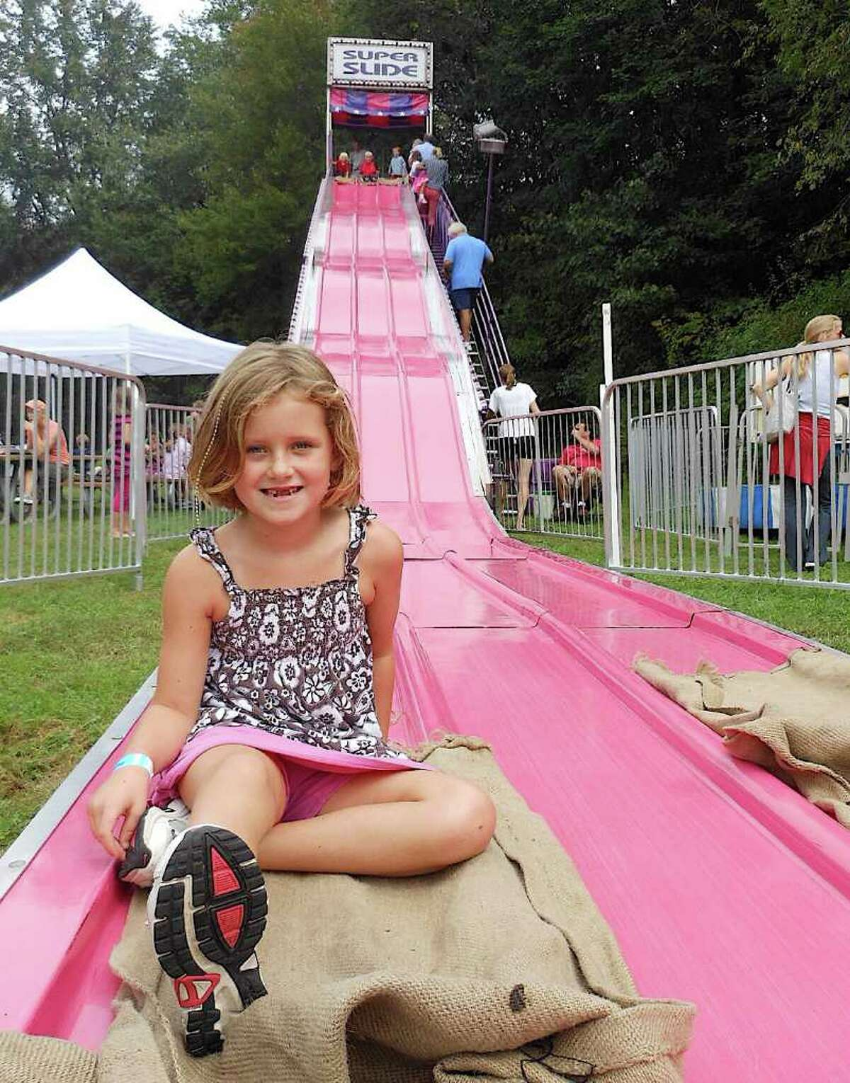 Madeline Reed, 7, a second-grader at Dwight School, smiles after a ride down the Super Slide at the school fair.