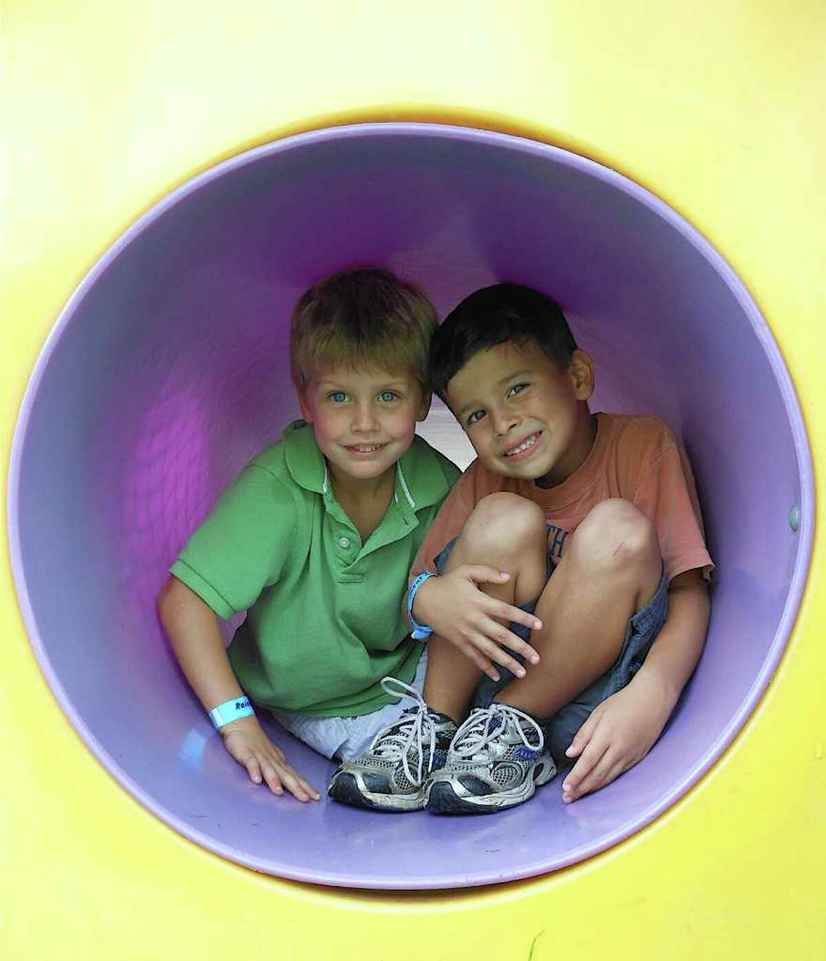 Henry Kelly and Gavin McGuire, both 5-year-old kindergarten students at Dwight School, squeeze through a tube at teh school fair Saturday. Henry's mother, Stephanie, Dwight PTA president elect.