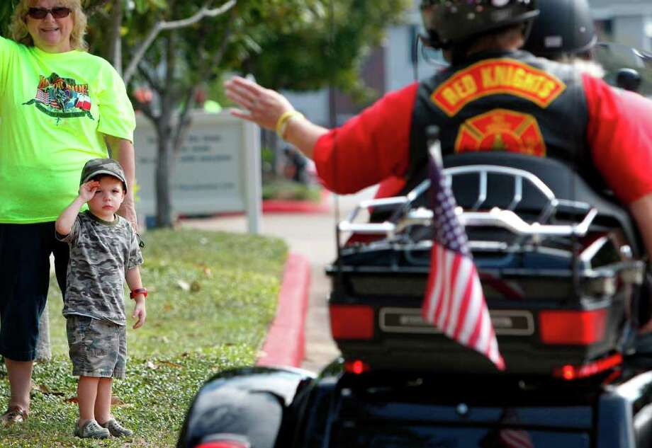 Lois Roberts stands next to her grandson Darrell Roberts, 3, who is saluting motorcyclists participating in the 6th Annual Texas Honor Ride Main Fundraiser at West Conroe Baptist Church on Saturday, Sept. 24, 2011, in Conroe. The Texas Honor Ride is a non-profit organization and expects to fundraise $30,000. All proceeds will go to help support Wounded Warriors and their families at Brooke Army Medical Center. Photo: Mayra Beltran, Houston Chronicle / © 2011 Houston Chronicle