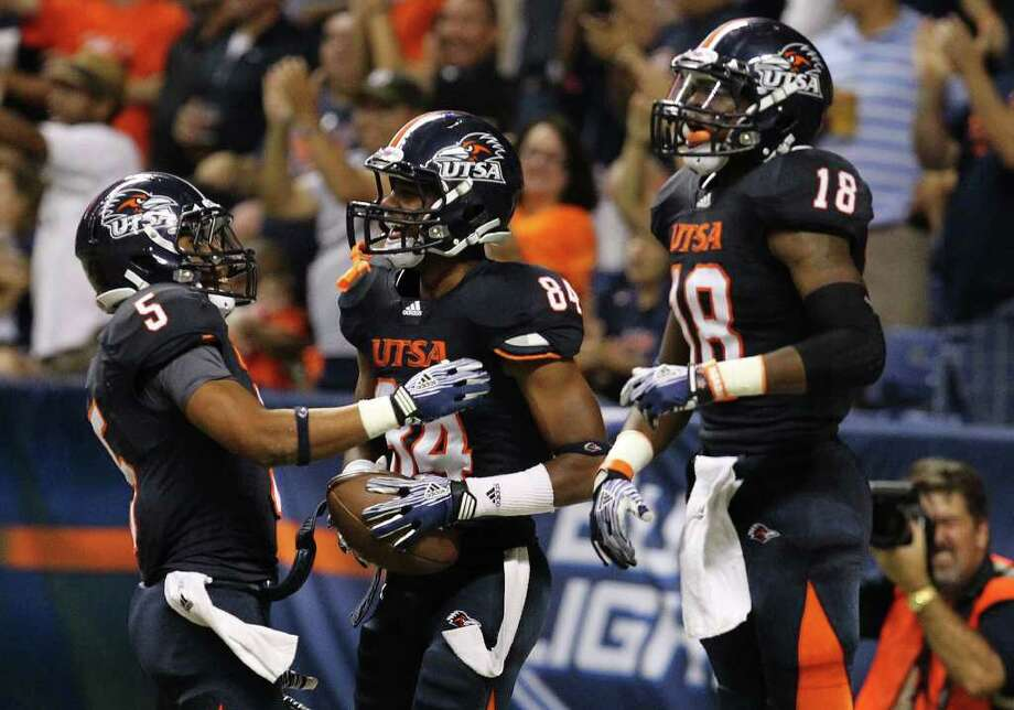 UTSA's Brandon Freeman (84) gets congratulated by teammates Brandon Armstrong (05) and Kenny Harrison (18) after Freeman scored on a 63-yard pass reception against Bacone in the first half at the Alamodome on Saturday, Sept. 24, 2011. Kin Man Hui/kmhui@express-news.net Photo: KIN MAN HUI, Express-News / SAN ANTONIO EXPRESS-NEWS