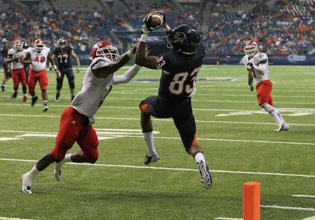 UTSA's Mike Wilburn (83) snags a pass over Bacone's Chase Rettig (05) for a touchdown in the second half at the Alamodome on Saturday, Sept. 24, 2011. UTSA defeated Bacone, 54-7. Kin Man Hui/kmhui@express-news.net Photo: KIN MAN HUI, Express-News / SAN ANTONIO EXPRESS-NEWS