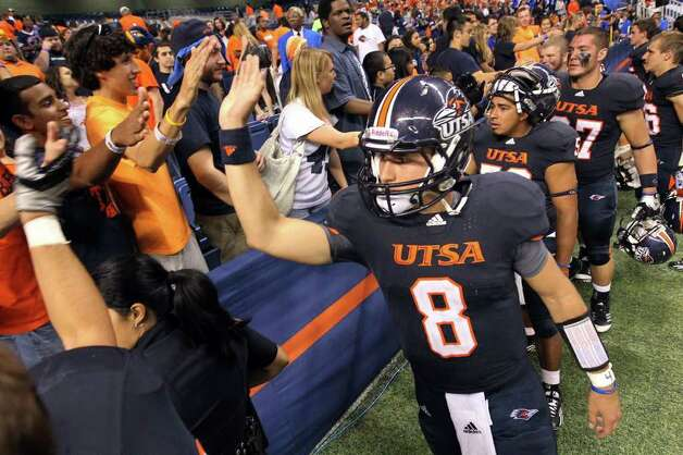 UTSA's Eric Soza (08) joins other players in high-fiving fans after their victory against Bacone at the Alamodome on Saturday, Sept. 24, 2011. UTSA defeated Bacone, 54-7. Kin Man Hui/kmhui@express-news.net Photo: KIN MAN HUI, Express-News / SAN ANTONIO EXPRESS-NEWS