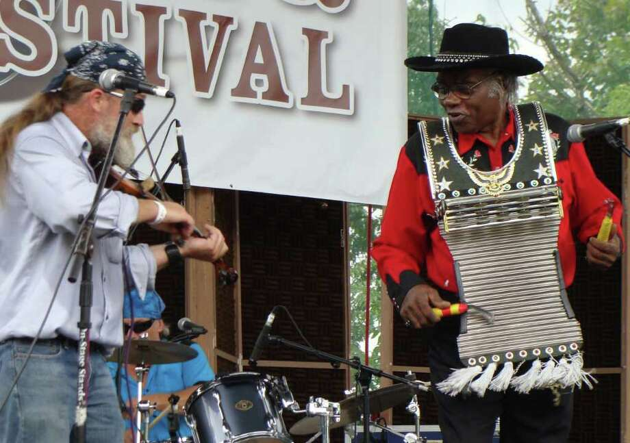"""Professorî Jim Porter, right, a Louisiana musician now living in New York, performed on a rub board, or frottoir, with River City Slim & the Zydeco Hogs Saturday at the 4th annual Blues, Views & BBQ Festival in downtown Westport. Photo: Meg Barone / Westport News freelance"