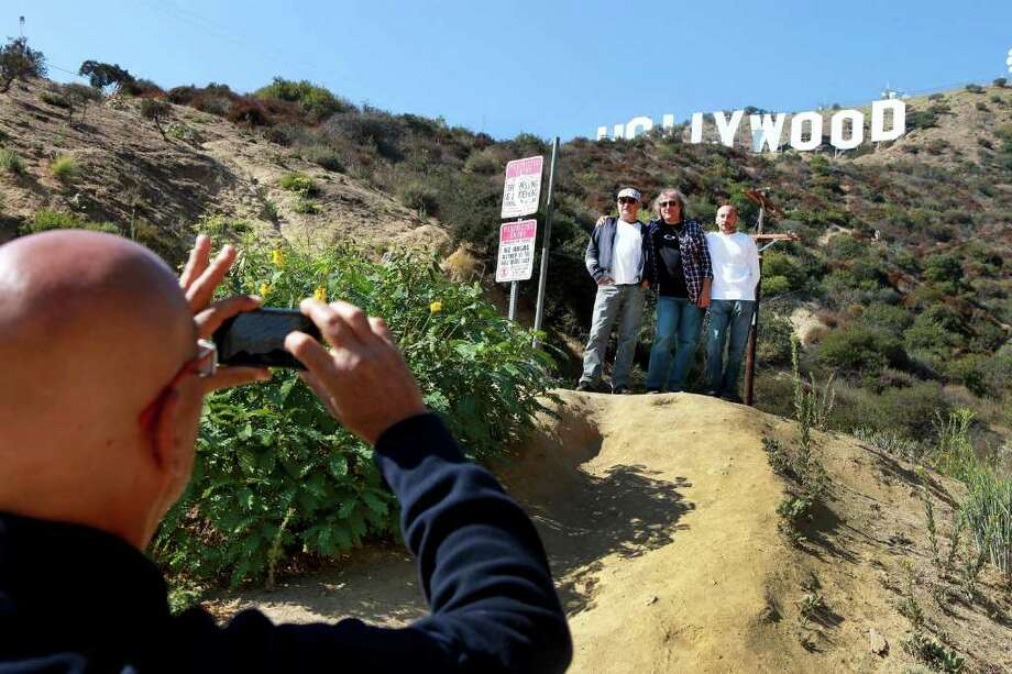 MONICA ALMEIDA : NEW YORK TIMES NO EIFFEL TOWER: French tourists pose beneath the Hollywood sign in a restricted area in Los Angeles, a growing activity that has prompted a feud between two community groups. Photo: MONICA ALMEIDA / NYTNS
