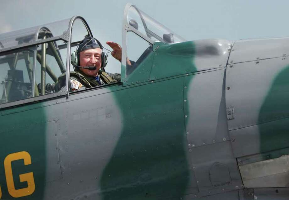 Retired Lt. Col. Ted Wolfram III, of Spring, waves to family members as he gets ready to fly the T-6 Texan, the same plane he used to fly while in the Air force back in 1944, at Ellington Field. Photo: Mayra Beltran, Houston Chronicle / © 2011 Houston Chronicle