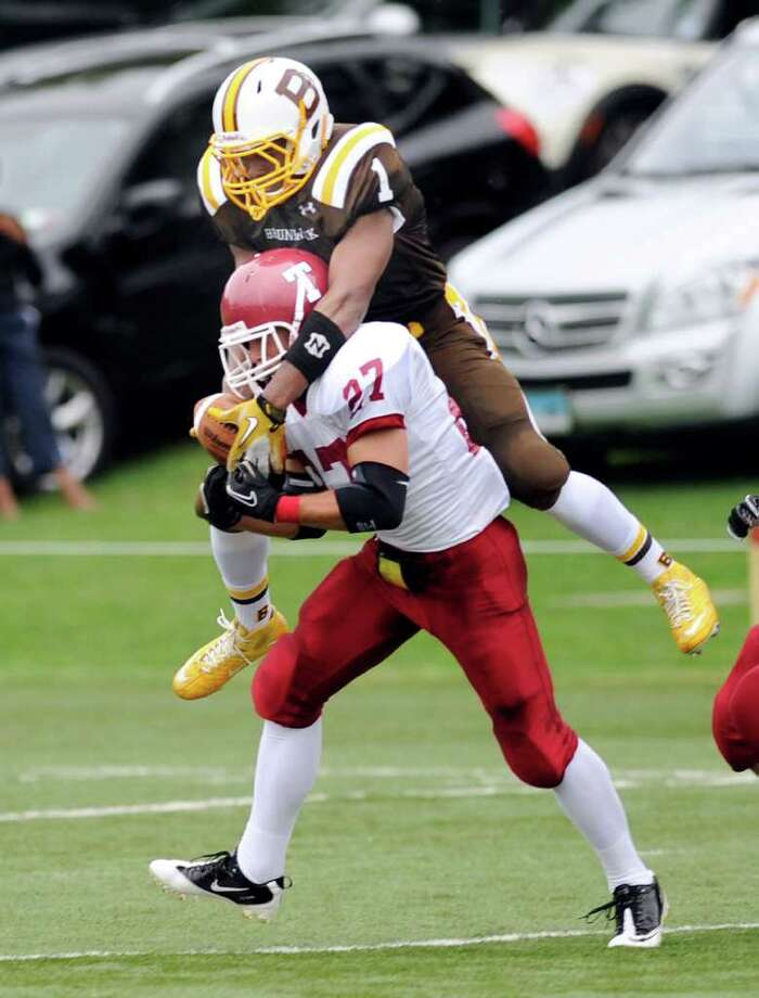 Dontqutae Robinson, top, # 1, of Brunswick School, reaches over Taft defender, John Zakrzewski, # 27, to make a spectacular catch during Football game between Brunswick School and Taft at Brunswick School, Greenwich, Saturday afternoon, Sept. 24, 2011. Photo: Bob Luckey / Greenwich Time