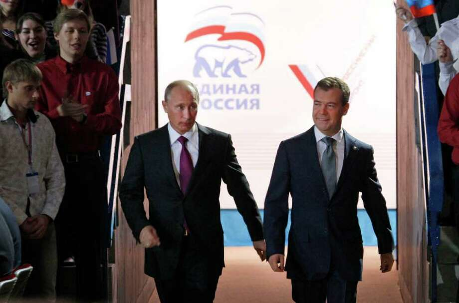 IVAN SEKRETAREV : ASSOCIATED PRESS BACK TO NO. 1: Prime Minister Vladimir Putin, left, and Russian President Dmitry Medvedev arrive Saturday at a United Russia party congress. Party members greeted the news of Putin's designs on the presidency with extended applause. Photo: Ivan Sekretarev / AP