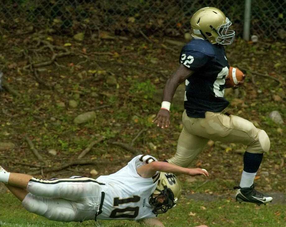 Notre Dame's Nigel Beckford, right, runs the ball past Joel Barlow's Jack Shaban during their game at Notre Dame Catholic High School in Fairfield on Saturday, Sept. 24, 2011. Photo: Jason Rearick / The News-Times