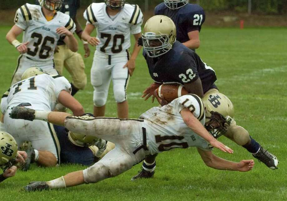 Joel Barlow's Jack Shaban, diving, unsucessfully tackles Notre Dame's Nigel Beckford during their game at Notre Dame Catholic High School in Fairfield on Saturday, Sept. 24, 2011. Photo: Jason Rearick / The News-Times