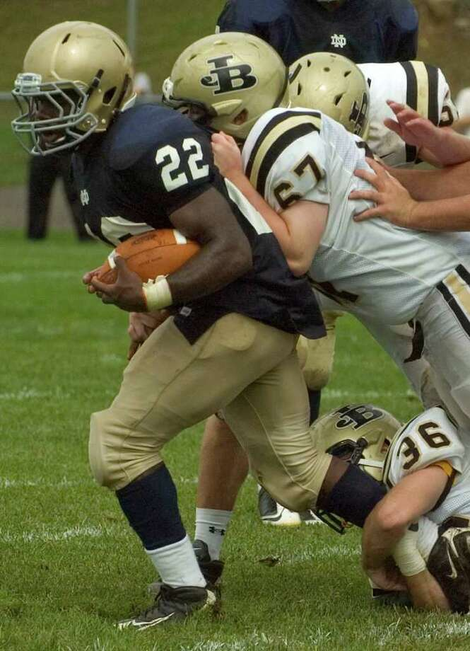 Notre Dame's Nigel Beckford, left, runs through the middle with Joel Barlow's Joseph Socci(67) and Zach Cordelli(36) hanging on during their game at Notre Dame Catholic High School in Fairfield on Saturday, Sept. 24, 2011. Photo: Jason Rearick / The News-Times