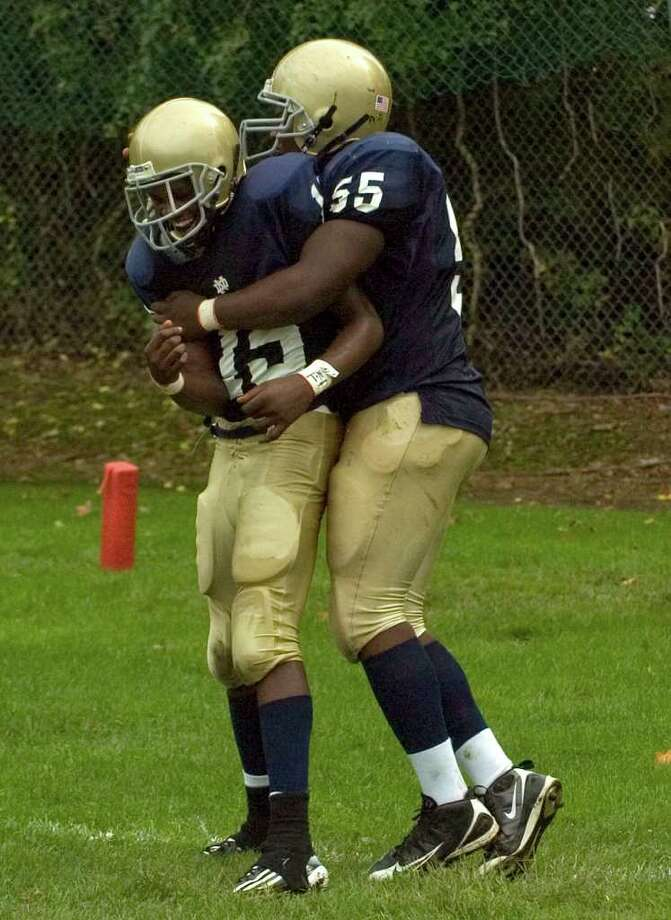 Notre Dame's Theo Tumba, right, congratulates Glody Tumba after Glody's touchdown during their game against Joel Barlow at Notre Dame Catholic High School in Fairfield on Saturday, Sept. 24, 2011. Photo: Jason Rearick / The News-Times
