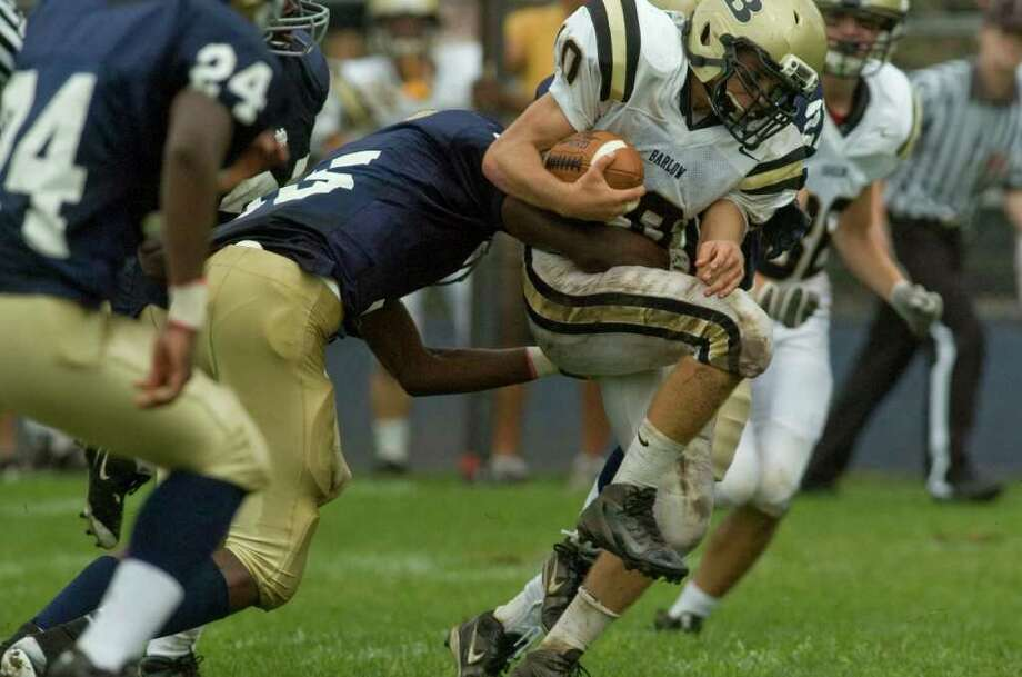 Notre Dame's Glody Tumba tries to bring down Joel Barlow's Jack Shaban during their game at Notre Dame Catholic High School in Fairfield on Saturday, Sept. 24, 2011. Photo: Jason Rearick / The News-Times