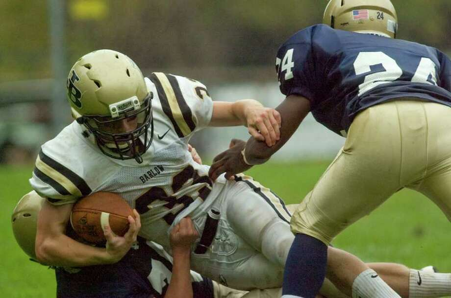 Joel Barlow's Steven Miller, center, is brought down by Notre Dame's Tyler Doy, left, with help from Brandon Thompson, right, during their game at Notre Dame Catholic High School in Fairfield on Saturday, Sept. 24, 2011. Photo: Jason Rearick / The News-Times