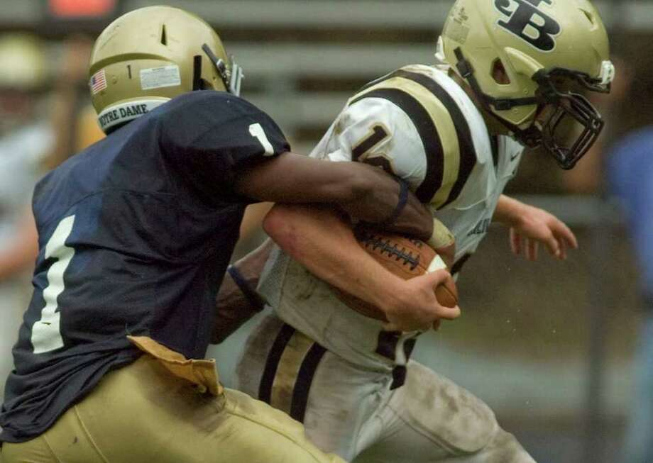 Notre Dame's Daquan Coleman, left, tries to strip the ball from Joel Barlow quarterback Jack Shaban during their game at Notre Dame Catholic High School in Fairfield on Saturday, Sept. 24, 2011. Photo: Jason Rearick / The News-Times