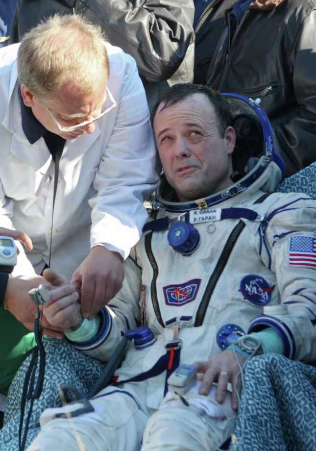 Russian space agency rescuers assist astronaut Ron Garan after his return to Earth this month. Photo: SERGEI ILNITSKY / AFP