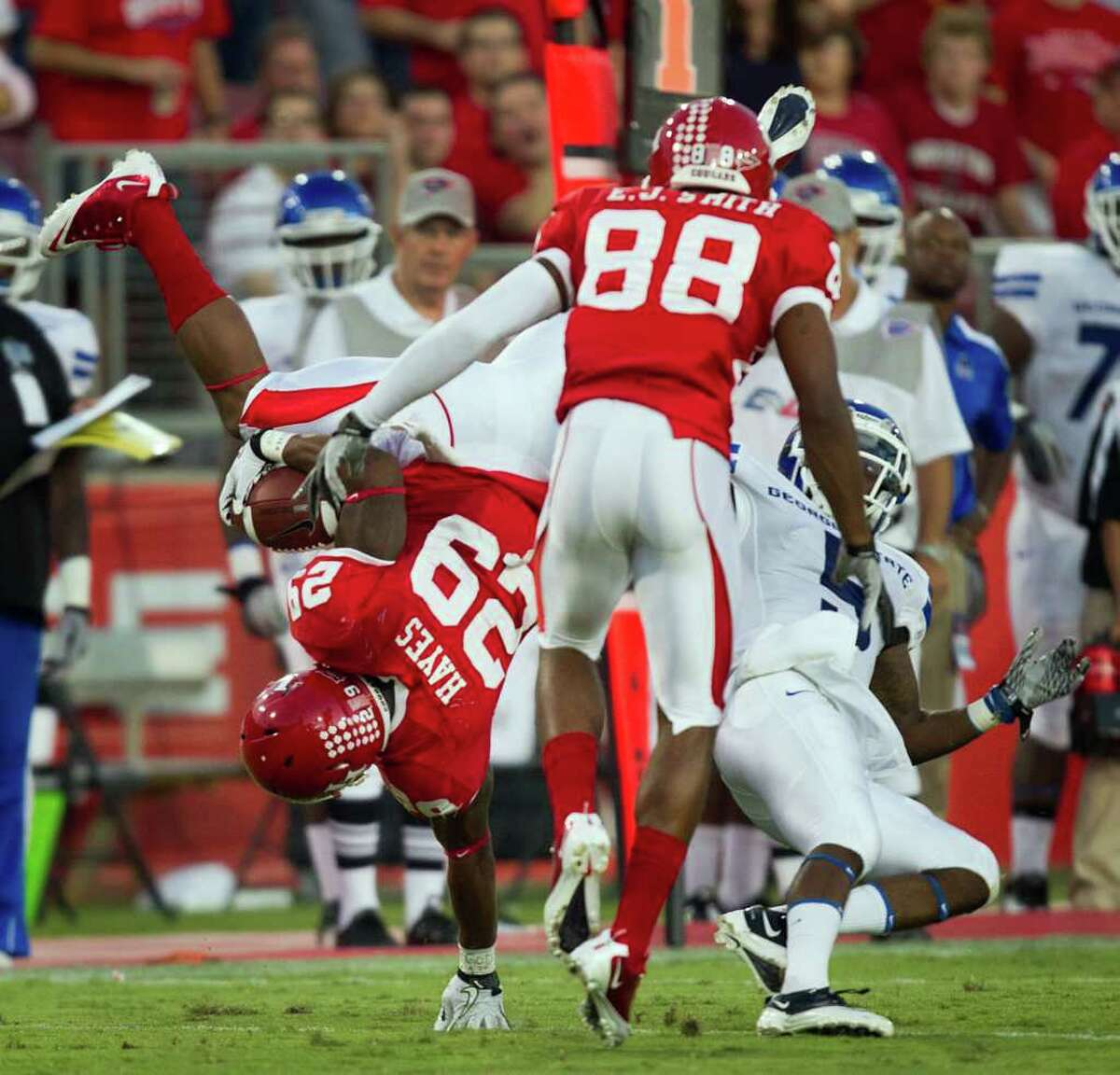 Houston Cougars running back Michael Hayes (29) flips over Georgia State Panthers cornerback Demarius Matthews (5) as wide receiver E.J. Smith (88) looks on during the first half of an NCAA football game at Robertson Stadium, Saturday, Sept. 24, 2011, in Houston.