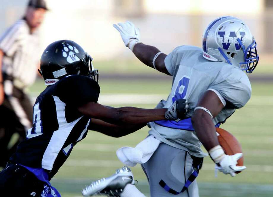 Halfback Jailin Singleton #9 of the Westbury Rebels rushes against defensive back Aston Palacious #13 of the Westside Wolves of in a District 20-5A high school football game at Butler Stadium in Houston, Texas.: Thomas B. Shea Photo: For The Chronicle: Thomas B. She