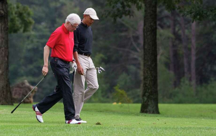 EVAN VUCCI: ASSOCIATED PRESS POWER PLAYERS: President Barack Obama talks with former President Bill Clinton during a game of golf Saturday at Andrews Air Force Base. No word on who won, or the scores. Photo: Evan Vucci / AP