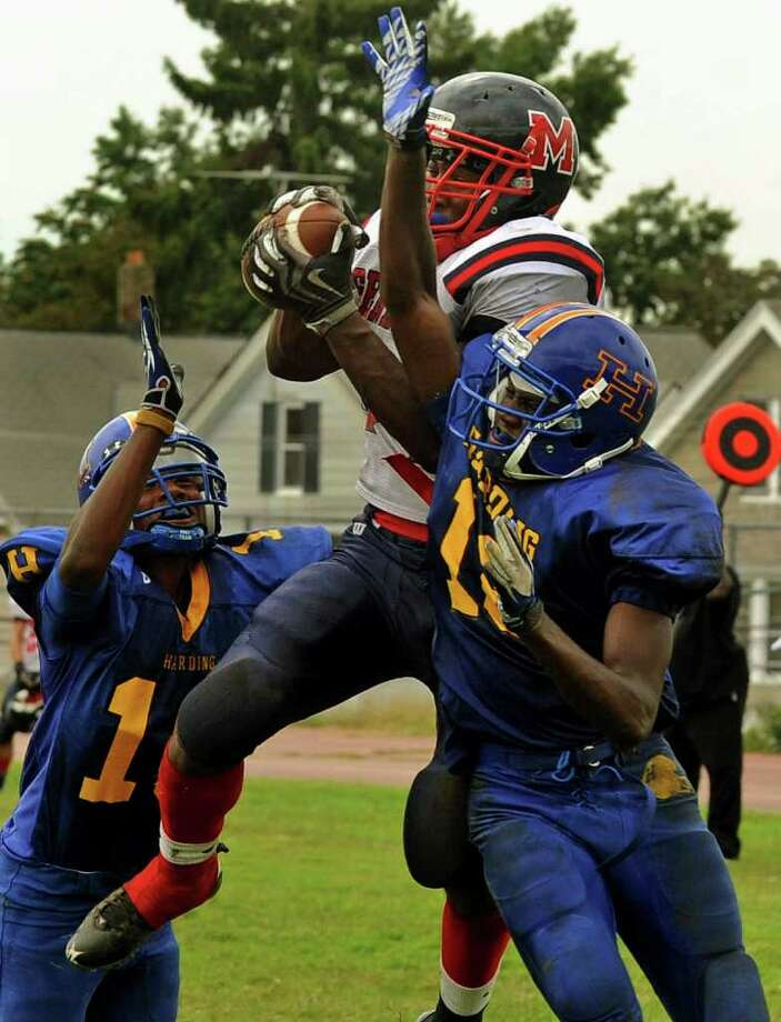 McMahon's #34 Chris Jerome catches the ball in the endzone for a touchdown during boys football action against Harding in Bridgeport, Conn. on Saturday September 24, 2011. Harding players are Jahaad Williams, left, and Antwaine Clark, right. Photo: Christian Abraham / Connecticut Post