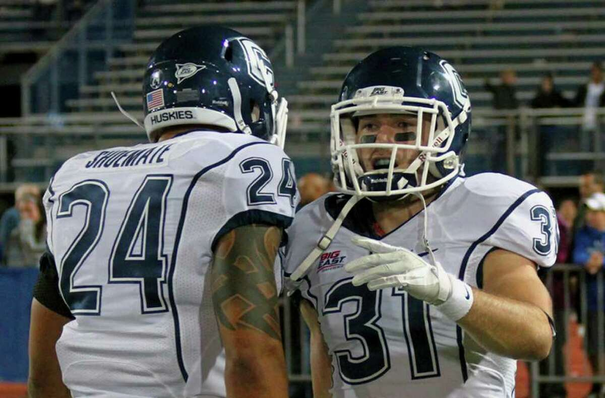 UConn's D.J. Shoemate congratulates teammate Nick Williams on his touchdown that gave them a 17-3 lead against Buffalo in Amherst, N.Y., Saturday. Connecticut won 17-3.