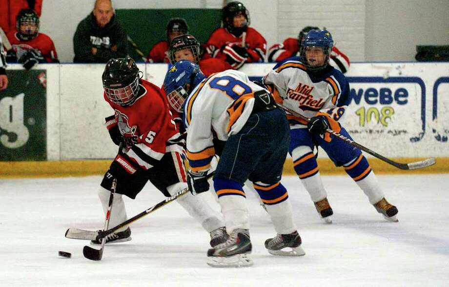 Pee Wee hockey action between Stamford and Mid-Fairfield at Twin Rinks complex in Stamford, Conn. on Saturday September 10, 2011. Stamford's #15 Everett Dolan, left, tries to control the puck as Mid-Fairfield's #8 Shea Courtmanche intercepts. Photo: Christian Abraham / Connecticut Post