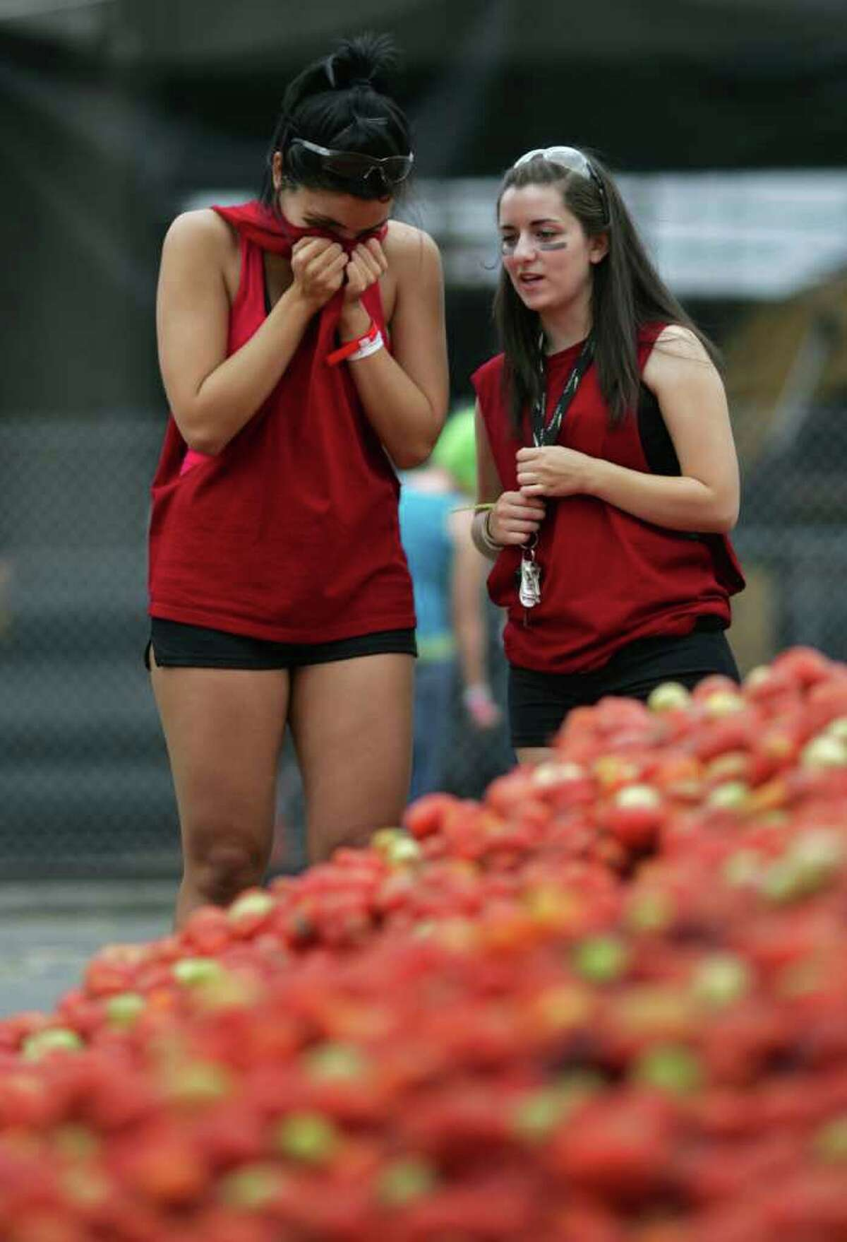 Alex Gramling, 21, left, covers her nose against the smell of 300,000 pounds of overripe tomatoes with her friend, Laura Van Kolck.