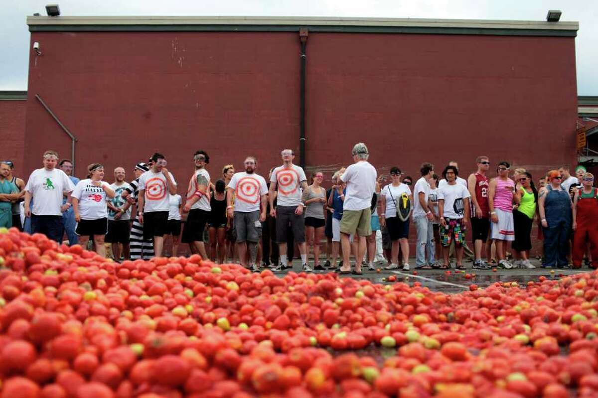 Hundreds of attendees wait before 300,000 pounds of overripe tomatoes.