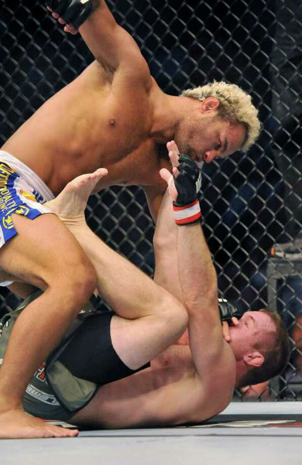 Josh Koscheck, left, of Fresno, Calif., pins Matt Hughes, of Hillsboro, Ill., to the mat during their UFC Welterweight bout, Saturday, Sept. 24, 2011, in Denver. Koscheck won the fight. (AP Photo/ Jack Dempsey ) Photo: Jack Dempsey, Associated Press / FR42408 AP