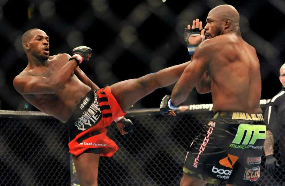 Jon Jones, left, of Endicott, N.Y., gets in a kick to the head of Rampage Jackson, of Irvine, Calif., during the first round of their UFC Light Heavyweight title bout, Saturday, Sept. 24, 2011, in Denver.  (AP Photo/ Jack Dempsey ) Photo: JACK DEMPSEY, Associated Press / FR42408 AP