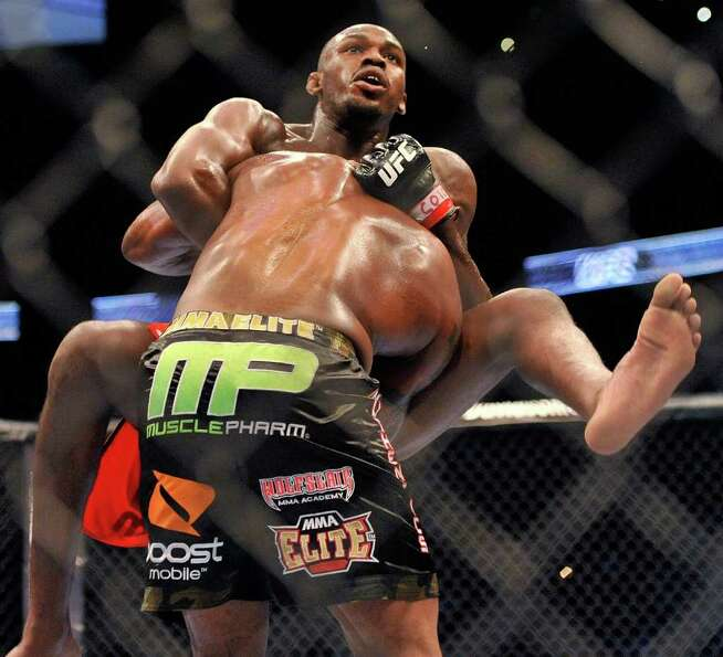 Jon Jones, top, of Endicott, N.Y., battles Rampage Jackson, of Irvine, Calif., during the third roun