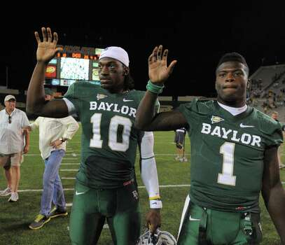 Baylor quarterback Robert Griffin III, left, and receiver wide receiver Kendall Wright, right, hold up their hands following their 56-31 win over Rice following an NCAA college football game on Saturday, Sept. 24, 2011, in Waco, Texas. (AP Photo/Rod Aydelotte) Photo: Rod Aydelotte, Associated Press / AP2011