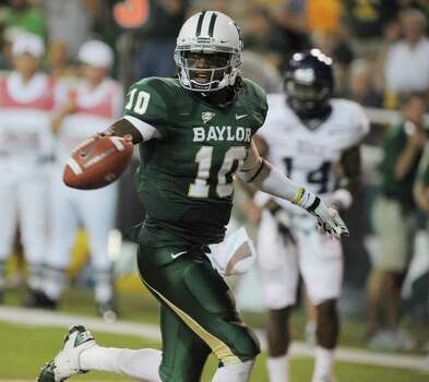 Baylor quarterback Robert Griffin III runs past Rice's Xavier Webb for a third quarter touchdown of an NCAA college football game on Saturday, Sept. 24, 2011, in Waco, Texas.  Baylor won 56-31.(AP Photo/Rod Aydelotte) Photo: Rod Aydelotte, Associated Press / AP2011