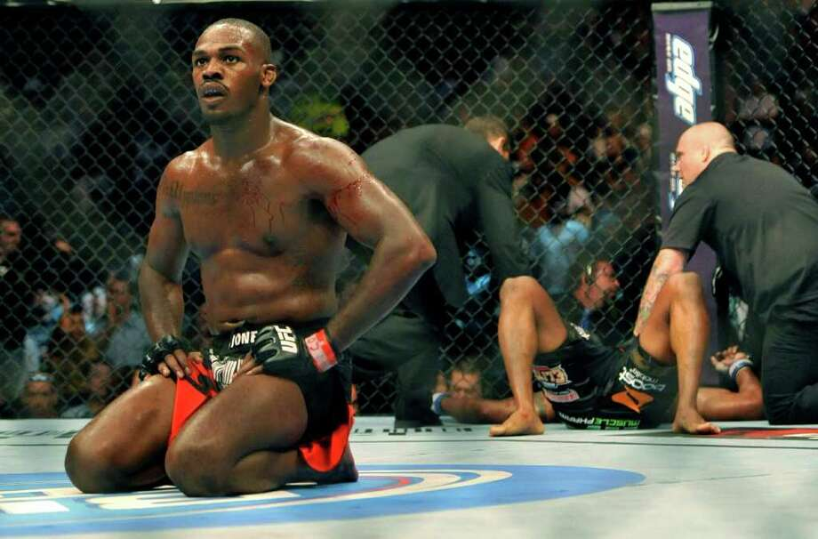 Jon Jones, left, of Endicott, N.Y., kneels in the center of the rink after knocking out Rampage Jackson, right, of Irvine, Calif., during the fourth round of their UFC Light Heavyweight title bout, Saturday, Sept. 24, 2011, in Denver. Jones won the fight with a knockout in the fourth round. (AP Photo/ Jack Dempsey ) Photo: Jack Dempsey, Associated Press / FR42408 AP