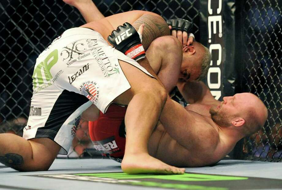 Mark Hunt, top, of Sydney, Australia, and Ben Rothwell, of Kenosha, Wis., battle it out during their UFC Heavyweight bout, Saturday, Sept. 24, 2011, in Denver. Hunt won the fight. (AP Photo/ Jack Dempsey ) Photo: JACK DEMPSEY, Associated Press / FR42408 AP