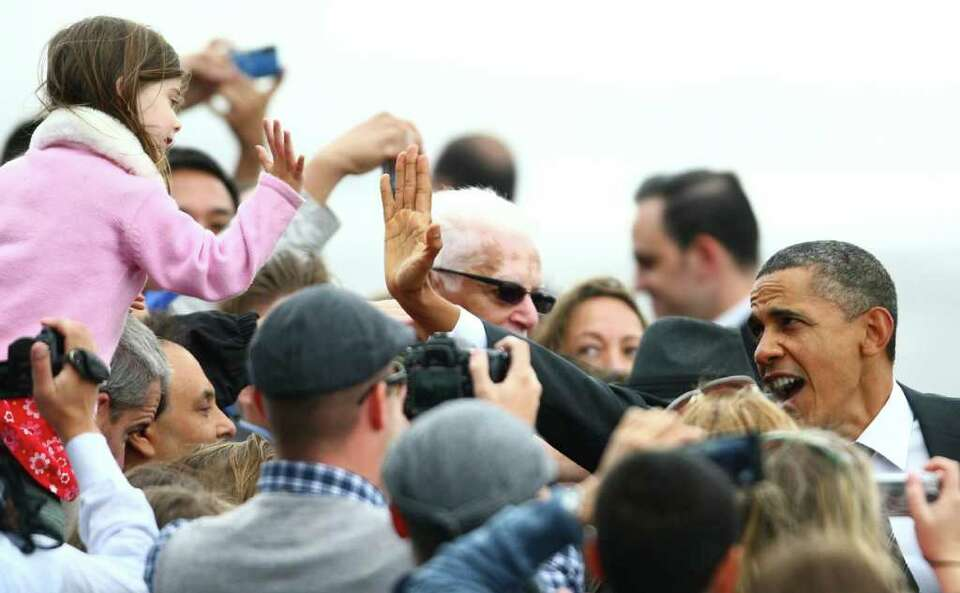 President Barack Obama high-fives a young supporter after he departed Air Force One at Boeing Field