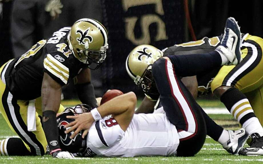 Houston Texans quarterback Matt Schaub (8) holds his head after he is hit by New Orleans Saints strong safety Roman Harper (41) and New Orleans Saints nose tackle Sedrick Ellis, right, during the fourth quarter of an NFL football game at the Louisiana Superdome Sunday, Sept. 25, 2011, New Orleans. The Saints beat the Texans 40-33. Photo: Brett Coomer, Houston Chronicle / © 2011 Houston Chronicle