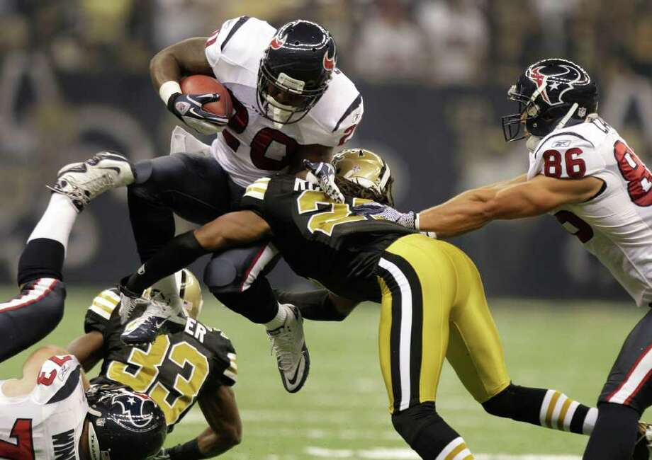 Texans running back Steve Slaton is stopped at the line of scrimmage by Saints cornerback Patrick Robinson on Sunday in New Orleans. Photo: Brett Coomer, Houston Chronicle / © 2011 Houston Chronicle