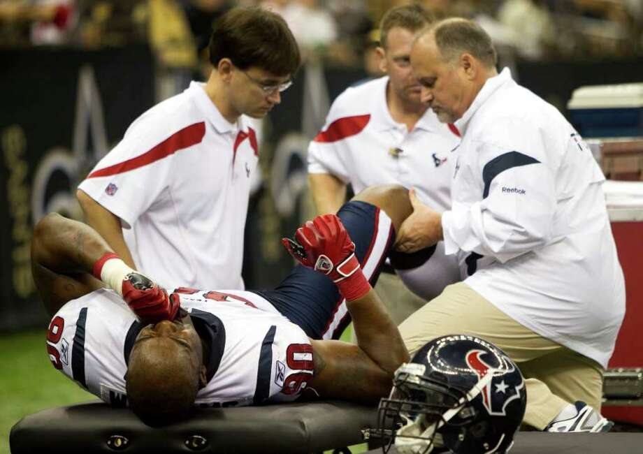 Houston Texans outside linebacker Mario Williams (90) has his knee checked on the sidelines during the third quarter of an NFL football game against the New Orleans Saints at the Louisiana Superdome Sunday, Sept. 25, 2011, New Orleans. Williams returned to the field later in the game. The Saints beat the Texans 40-33. Photo: Brett Coomer, Houston Chronicle / © 2011 Houston Chronicle
