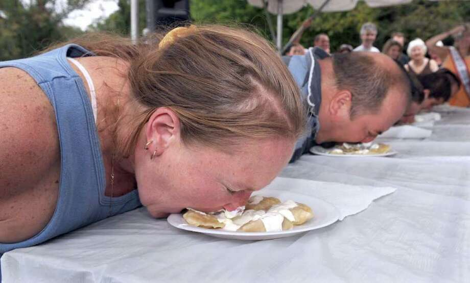 Trish Parker, left, of New Milford, and Tolik Yokovets of Bridgeport, dig in, hands behind their back,  at the start of the varynky eating contest at the annual Ukrainian Festival held at Paproski's Farm in Newtown Sunday.  Photo taken Sunday, Sept. 25, 2011. Photo: Carol Kaliff