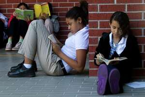 BRETT COOMER : CHRONICLE BOOK BREAK: Sixth-graders Kayla Houston, center, and Joceline Gonzalez read outside in the courtyard at Caraway Intermediate School. Students at the school are so hooked on reading they've even created weekly book clubs.