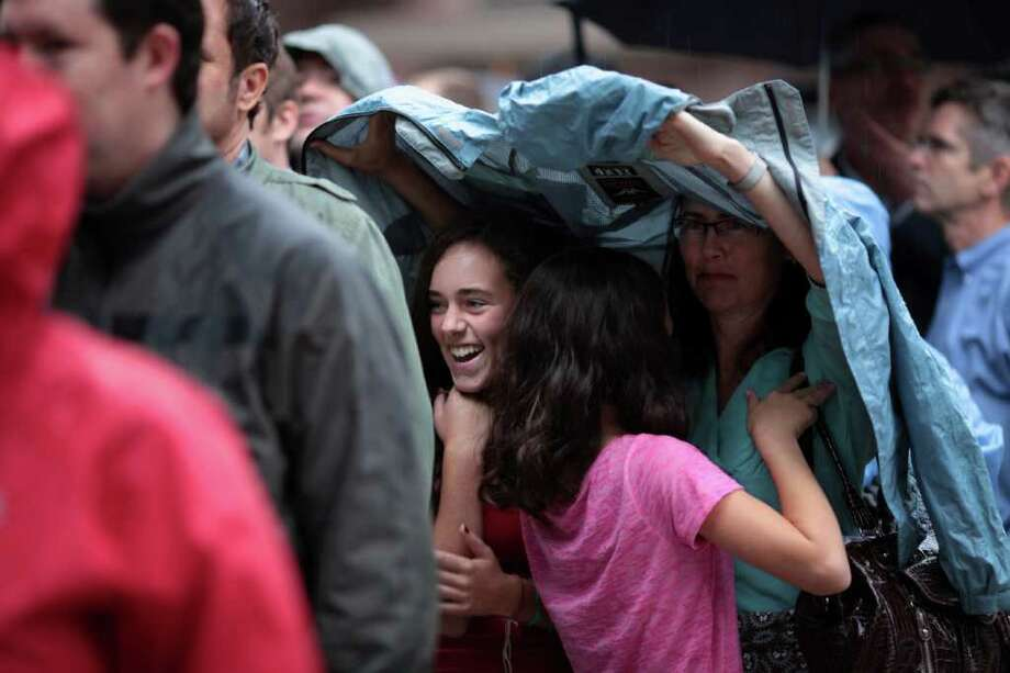 While waiting in line to hear President Barack Obama speak, Hazel Williams, left, laughs as her sister, Teddy Williams, center, attempts to avoid the rain by slipping under mother Diane Butler's coat. Photo: JORDAN STEAD / FOR SEATTLEPI.COM
