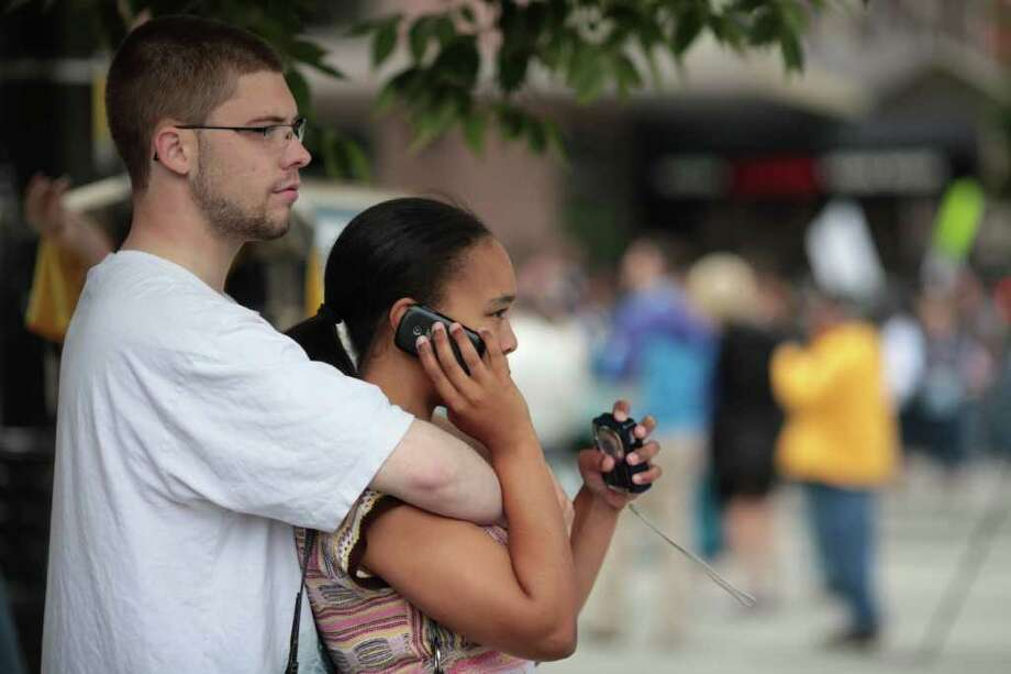 Kris Pehrson, left, and his girlfriend, Kendall Huff, right, watch protesters shout from the other side of the street near the Paramount Theatre. Photo: JORDAN STEAD / FOR SEATTLEPI.COM