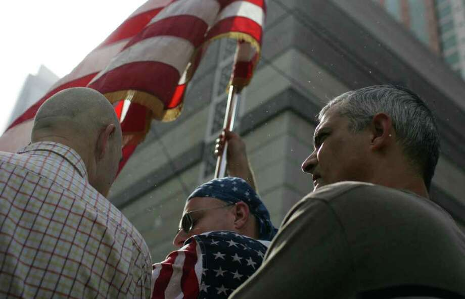 Anthony Hunter, right, watches a crowd line up to hear President Barack Obama speak while protester Dave Hobley, center, hoists a flag on Sunday near the Paramount Theatre. Photo: JORDAN STEAD / FOR SEATTLEPI.COM